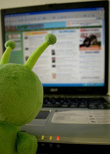 alien de peluche lee una pantalla
