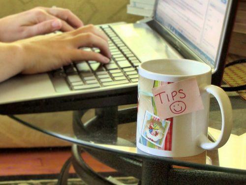 """manos tecleando en ordenador y taza con post-it que reza """"consejos"""""""
